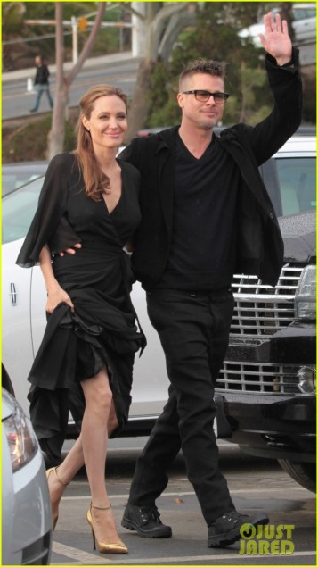 Angelina Jolie shows off both legs instead of one as she hikes up her skirt a little to avoid stepping on it as she and Brad Pitt leave the 2014 Spirit Awards in Santa Monica, Ca
